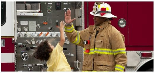 young child high-fiving a firefighter in front of a red fire engine