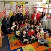 city representatives reading with school children in a classroom