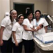 four nurses with a newborn in a hospital room