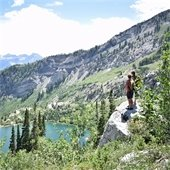 two hikers overlooking a mountain lake and valley
